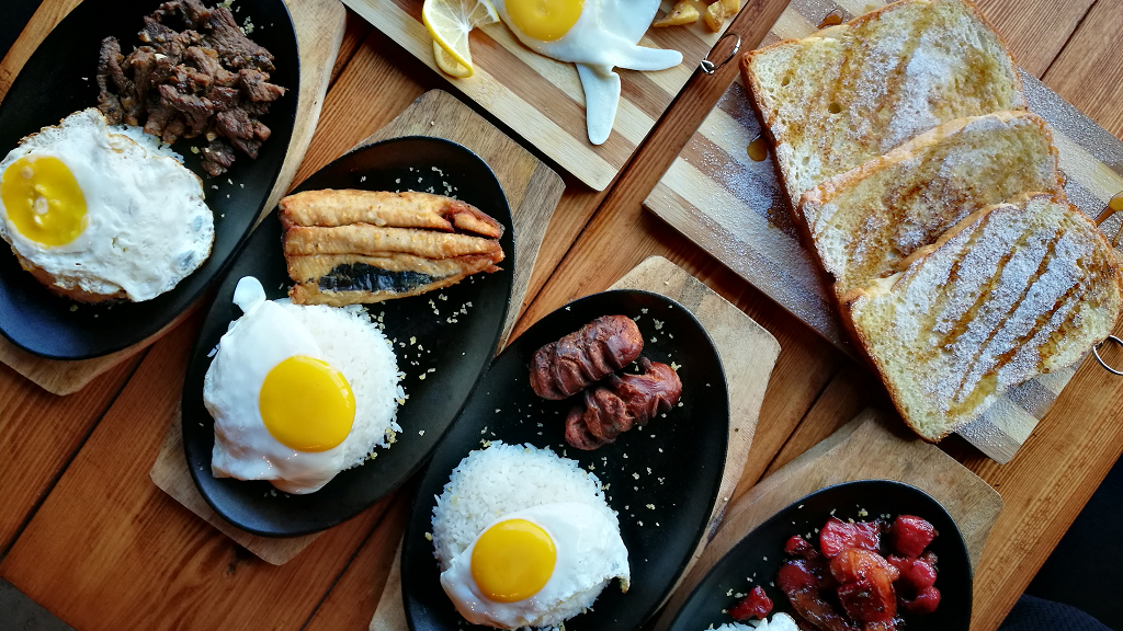 Poêles avec des œufs au plat et de la viande sur une table