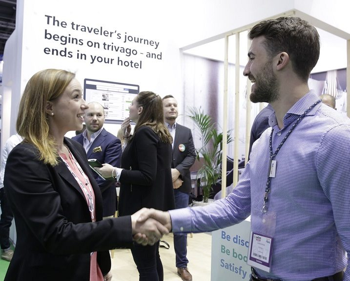a trivago expert shakes hands with a hotelier at the stand