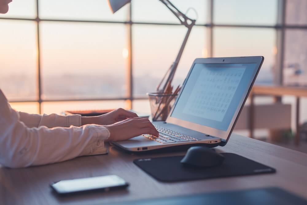 Un ordenador con unas manos escribiendo