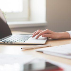 Photo mit Frau vor einem Laptop am Schreibtisch